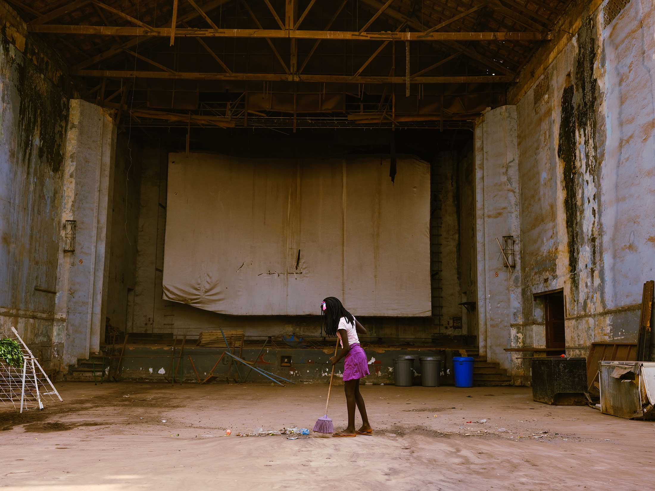 "A young girl sweeps the abandoned theater in downton Bissau. ""Women are the first to get up in the morning, and the last to go to bed at night"" is a phrase you hear female activists in the country say often as they fight for more representation at high levels of government."