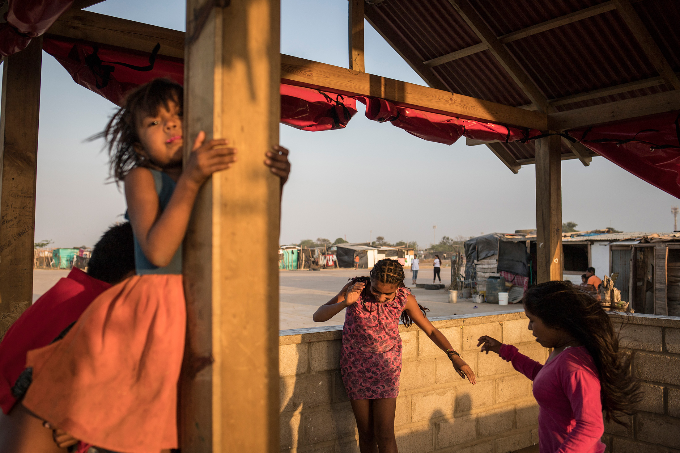 Children play in the La Pista migrant settlement, where Gomez often works with families.